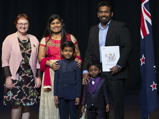 A family proudly displaying their citizenship certificate, alongside Deputy Mayor Sarah Free.