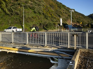 Photo taken on the seaward side of the bridge over the Kaiwharawhara Stream on Hutt Road showing the stream underneath, the bridge handrail, and beyond that, someone biking over the bridge and a white ute travelling along the road..