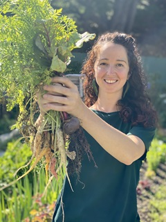 Image of Elza van Boxel of Seeds to Feeds holding fresh vegetables.