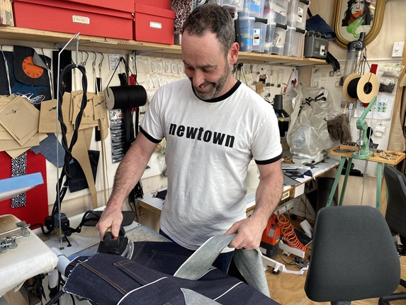 Newtown-based clothing designer Duncan McLean ironing cut demin for jeans he is making in his workroom.
