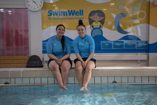 Aquatic Education Instructors Koopu Waipara and Milly Mackey, both 18, sit on the edge of the Tawa Pool smiling with their feet dangling in the water, with the colourful SwimWell sign behind.