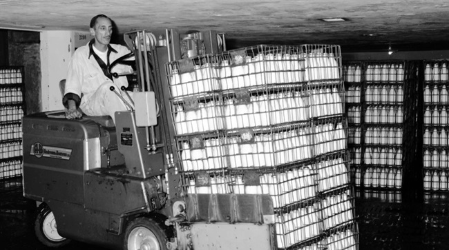 A man driving a forklift stacked with glass bottles filled with milk, surrounded by shelves also filled with milk bottles, at Wellington City Council's old Municipal Milk Department.
