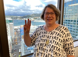 Rachel Noble in a white shirt with 'Yay' written all over it, smiling at the camera while doing sign language for 'Wellington', with the harbour in the background.