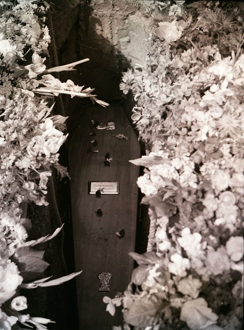 Black and white photograph of a coffin being lowered into a grave surrounded by flowers.