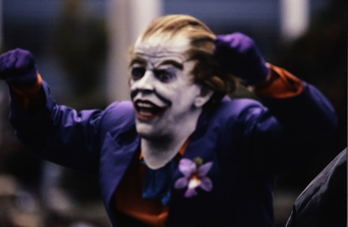 Photograph of a man wearing a creepy Joker mask and purple suit