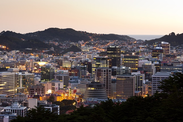 A stunning image of Wellington at dusk, with the Beehive in the foreground, Mount Victoria beyond, and a glimpse of ocean through the hills .