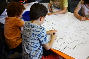 Four children from a Wellington primary school sitting at a table, drawing nature-inspired shapes on large pieces of white paper. These drawings inspired the designs on Wellington City Council's wall murals at Te Awe Library.