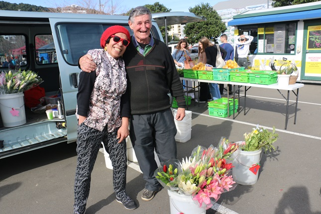 Tulelei and Tom Hayes, in an embrace smiling at the camera, in front of their van, with buckets of fresh flowers and citrus fruit surrounding them at Harbourside Market.