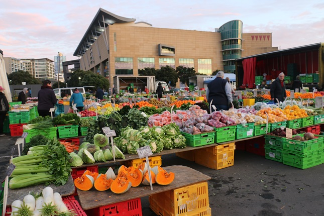 Image of bright fresh fruit and vegetables at the Harbourside Market on Wellington waterfront, with Te Papa in the background.