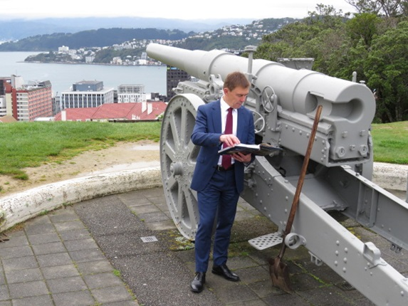 Mayor Andy Foster reading a book near a canon