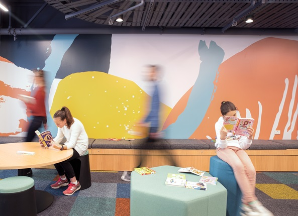 Two children sitting at separate tables, each engrossed in a book, with the bright Te Awe Library mural behind them and blurred people walking by.
