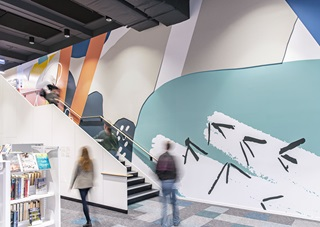 A floor-to-ceiling mural, featuring bright colours and nature-inspired shapes like bird footprints, alongside the stairwell at Te Awe Library.