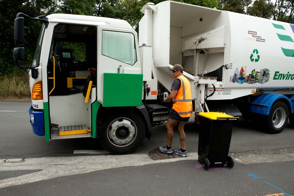 A recycling truck with a male staff member in a high vis, cap and sunnies, standing beside a wheelie bin on a dry road.
