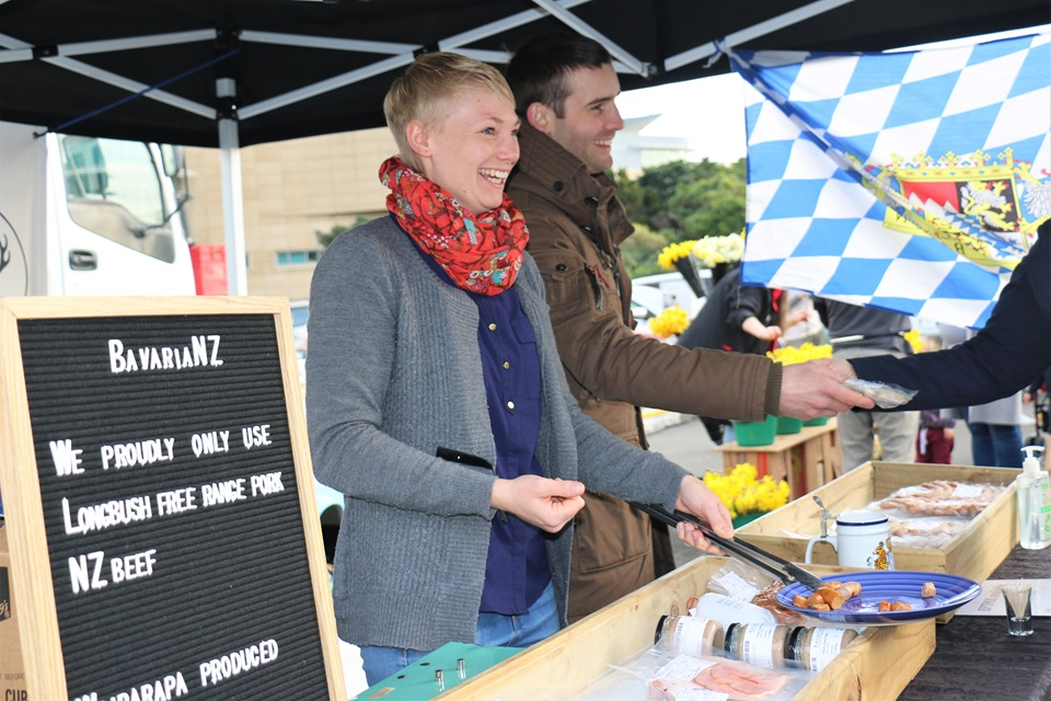 Lena Donandt with a big smile with a blue plate of cut up sausages, and Sebastian Nebel handing over some of his handmade German-style sausages to a customer, with a Bavarian flag hanging on the side of their marquee stall.