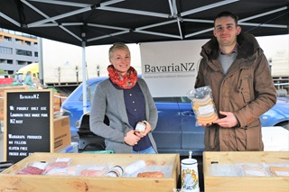 Young couple Lena Donandt and Sebastian Nebel standing on either side of their business sign, BavariaNZ, with their products, handmade German-style sausages, laid out in front of them in their marquee stall.