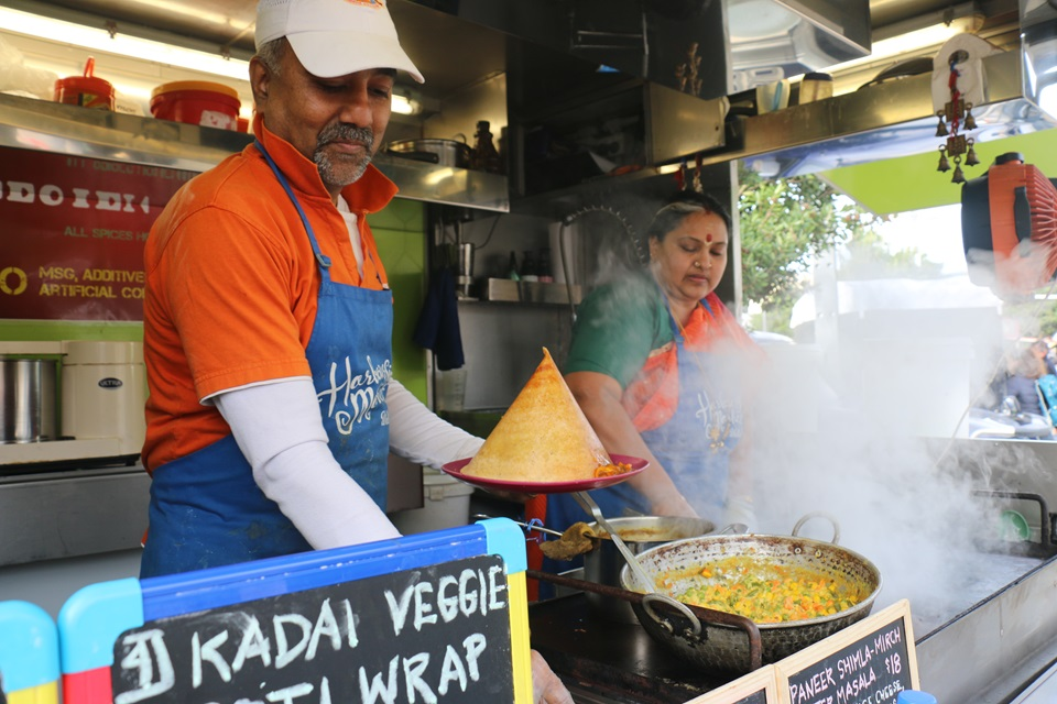 Balu Rajagopal wearing bright orange and blue serving up South Indian dosa and curry onto a plate, with his wife Shree Balasubramaniam to his right spreading batter onto a hotplate which is obscured by steam.