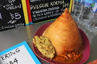 A close-up of a South-Indian masala dosa dish, which is a crunchy golden pancake, artfully rolled up to resemble a tent and placed on a pink plate on top of two tasty curries.