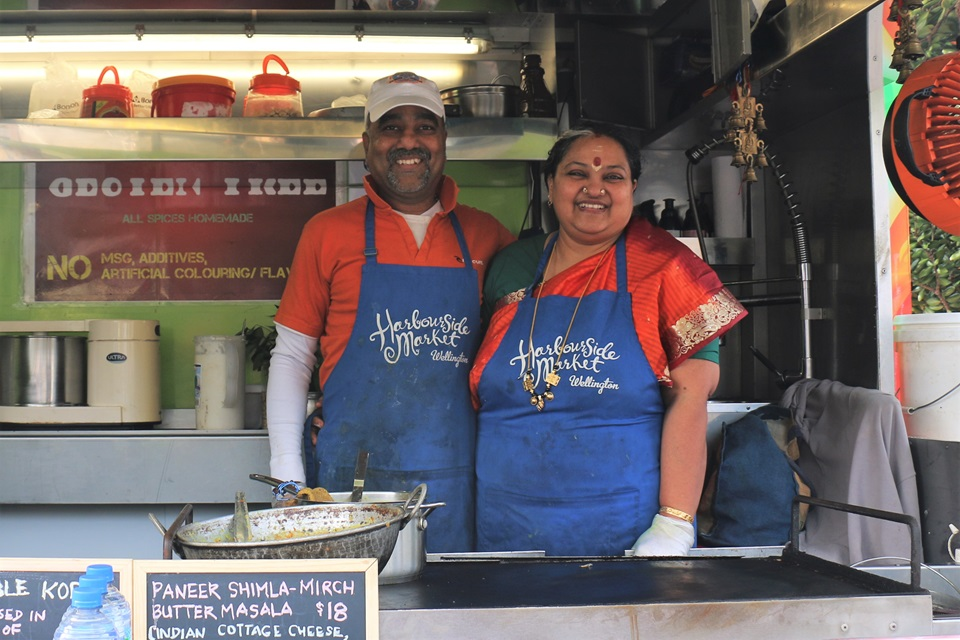 Husband and wife Balu Rajagopal and Shree Balasubramaniam, in orange t-shits and blue aprons, smiling from their food caravan, where they serve South Indian vegetarian food.