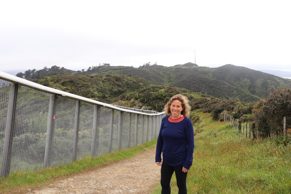 Brooklyn resident Mel Beirne in her running gear, standing to the right of the Zealandia fence line on the Brooklyn Wind Turbine Route, with hills and the turbine behind her.