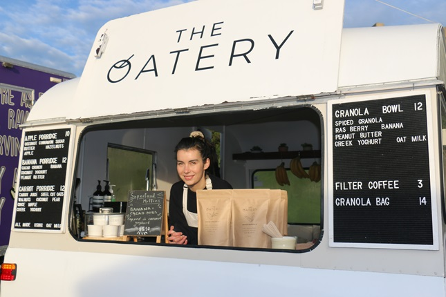 Anna Campbell looking out the front of her white caravan shop, The Oatery, where she sells porridge and granola bowls at Harbourside Market.