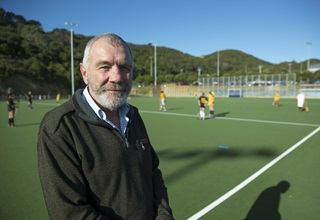 Peter Hemsley in front of a Council artificial turf.