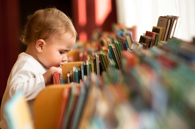 Young child looking at books.