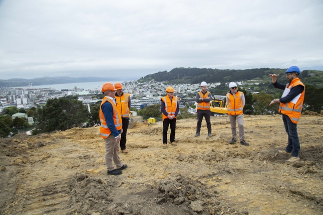 Six men in high-vis vests standing on top of the hillside above Prince of Wales Park, where construction has begun on Wellington's new Omāroro Reservoir, with city and harbour in background.