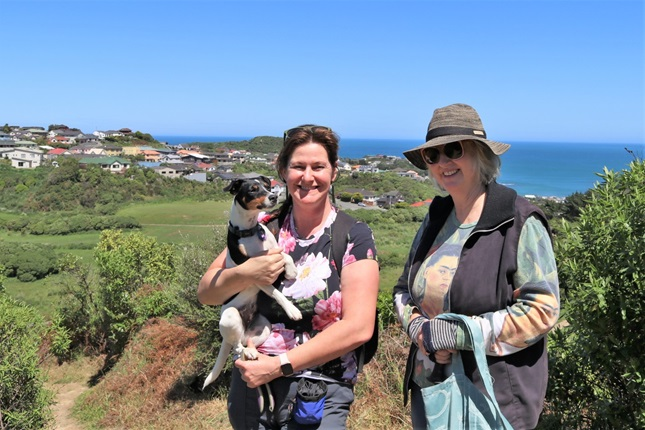Annie Yeates, holding her Fox Terrier, and Jenny Hartley standing in the sun on the top of Tawatawa Bush Track in Owhiro Bay, with housing and the ocean in the background.