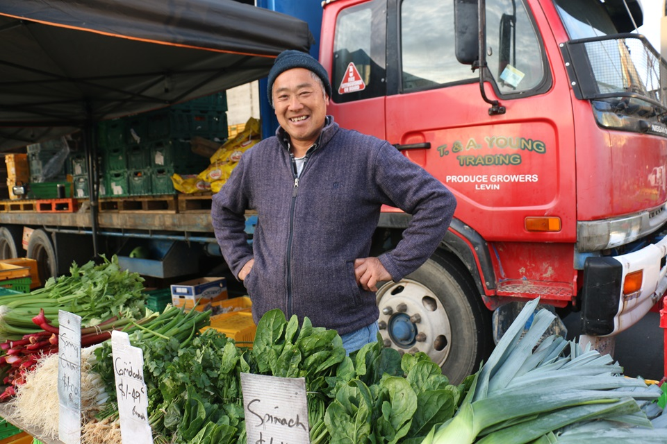 Tommy Young smiling with his hands on his hips, standing in front of his red truck, with a table of his home-grown vegetables in front of him at the Harbourside Market.