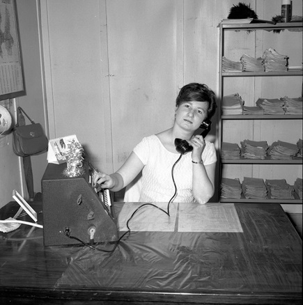 Black and white photo of woman using old telephone at desk in an office.