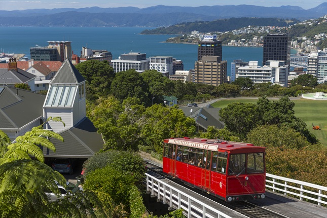 A shot of the red Cable Car on a sunny day, with Wellington buildings and the harbour in the background.