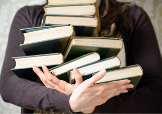 Person holding a stack of books.