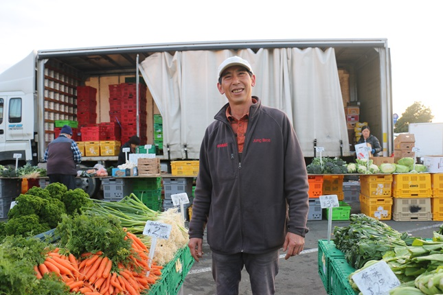 Tony Jung, a fresh produce grower from Levin, standing amongst his fresh vegetables in front of his truck filled with colourful crates at the Harbourside Market.
