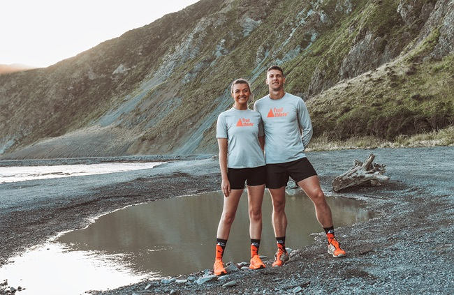Frieda and Hardus de Bruyn, wearing matching grey t-shirts, black shorts, and bright orange running shoes, standing together on the South Coast beach with Red Rocks behind them.