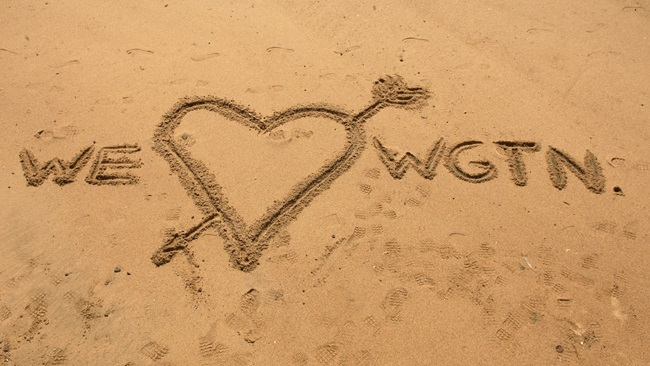 A love heart drawn in the sand with the words 'we' and 'Wellington' written on either side.