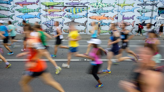 Blurred runners in bright activewear, jogging past the colourful shark mural opposite Waitangi Park.