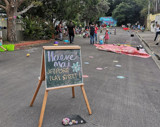 A chalkboard with the words 'haere mai', welcoming people to the Berhampore Play Day event, with lots of kids and adults playing on the street behind the sign.