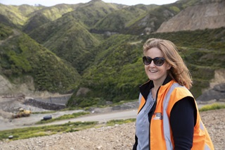 Emily Taylor-Hall, in her high-vis orange vest, smiling with the Southern Landfill and surrounding hills behind her.