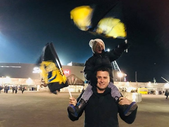 A young boy on his father's shoulders, both waving Hurricanes flags in support of the Wellington rugby team, outside Sky Stadium at night.