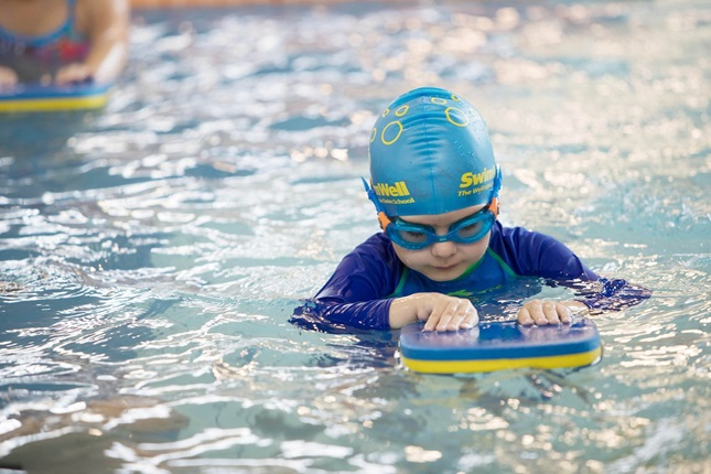 A young child with blue swimsuit, swimming cap and googles on, concentrating while using a flutter board in the pool.