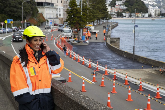 Engineer Veronica Byrne, dressed in a yellow hard hat and a hi-vis orange jacket, smiling while on the phone standing at a work site around Oriental Bay.
