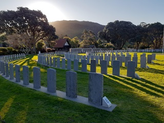 Anzac headstones in semi-circle lines at Karori Cemetery with sun shining over the hill.