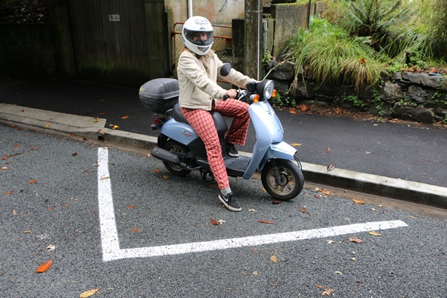 Victoria University student Daisy Lutyens on her scooter parked in a white triangle car park for small vehicles.