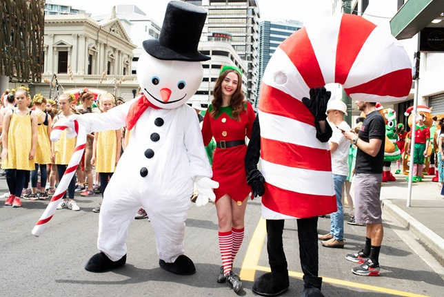 Performers dressed as a snowman, an elf, and a Candy cane pose for a photo at A very Welly Christmas.