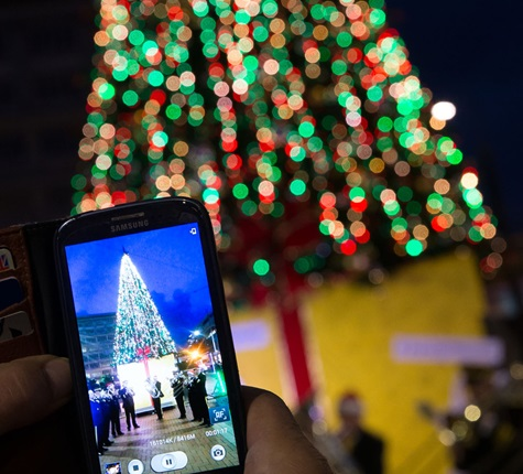 A Christmas tree at night time, all lit up with Christmas lights and someone standing in front of it taking a photo of it on their phone.