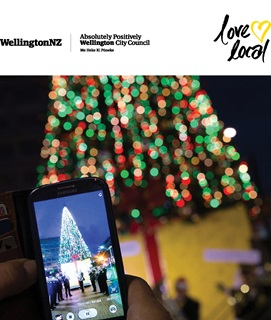 A Christmas tree at night time, all lit up with Christmas lights and someone standing in front of it taking a photo of it on their phone. Inset: WellingtonNZ, Absolutely Positively Wellington City Council, Love Local logos