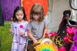 Two children with painted faces search through costume accessories.