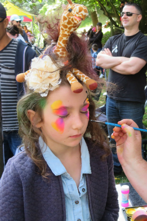A child getting their face painted.