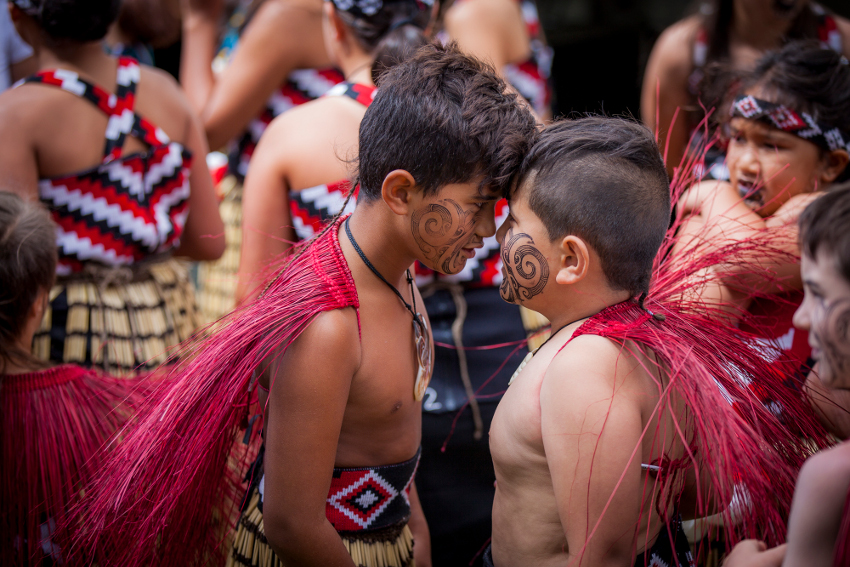 A hongi, traditional Māori greeting, between two children.