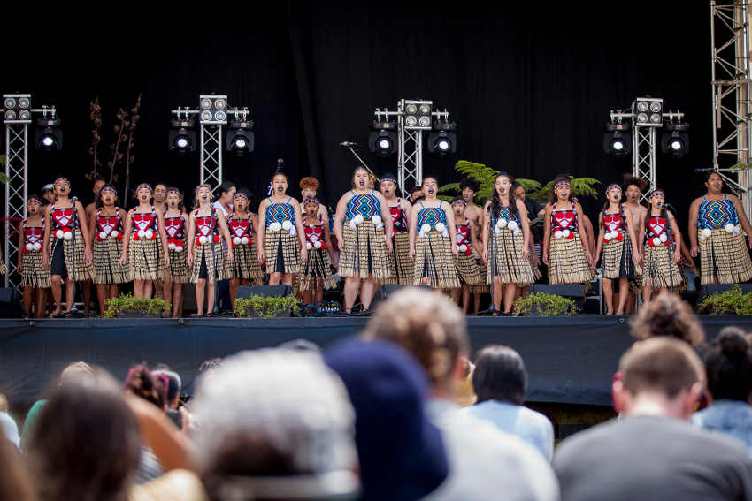 A group of children performing kapa haka on stage.